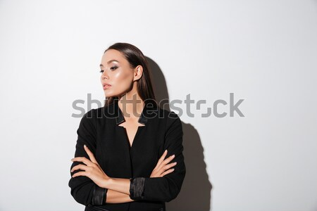 Young brunette woman in black suit standing with arms folded Stock photo © deandrobot