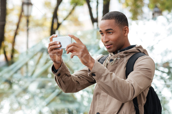 Young dark skinned man photographing outdoors with his cellphone Stock photo © deandrobot