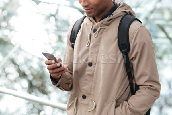 Cropped picture of skinned man with backpack chatting Stock photo © deandrobot