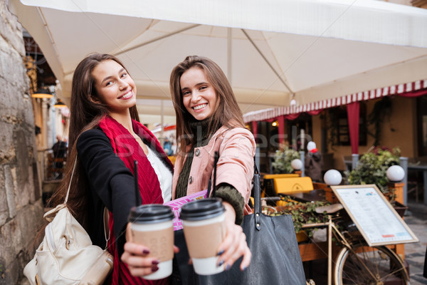 Two cheerful young women holding cups of coffee to go Stock photo © deandrobot