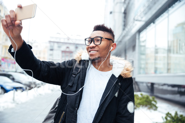 African cheerful man make a selfie while listening music outdoors. Stock photo © deandrobot