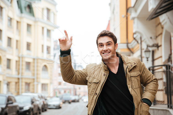 Happy young man catch the car. Stock photo © deandrobot