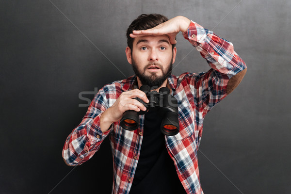 Man in plaid shirt holding binoculars and looking far away Stock photo © deandrobot