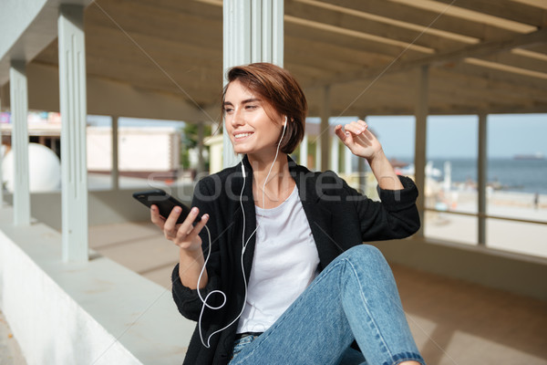 Cheerful woman listening to music from cell phone on terrace Stock photo © deandrobot