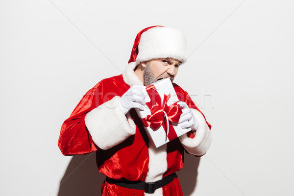 Angry man santa claus standing and biting gift box Stock photo © deandrobot