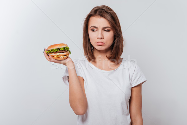 Confused young lady holding fastfood Stock photo © deandrobot