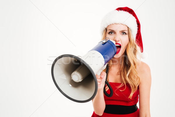 Angry young woman in santa claus costume shouting in megaphone Stock photo © deandrobot