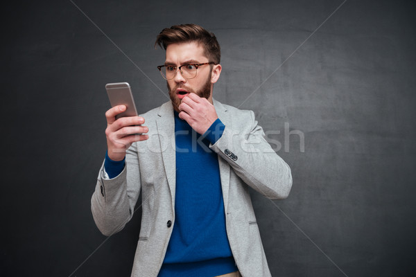 Thoughtful hipster with phone Stock photo © deandrobot