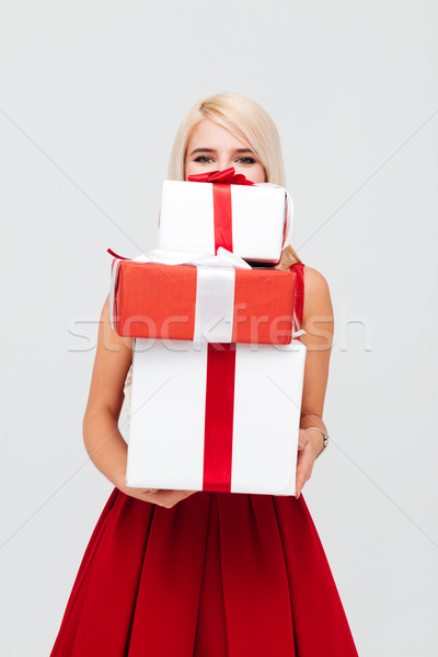 Woman in red dress peeking out from stack of presents Stock photo © deandrobot