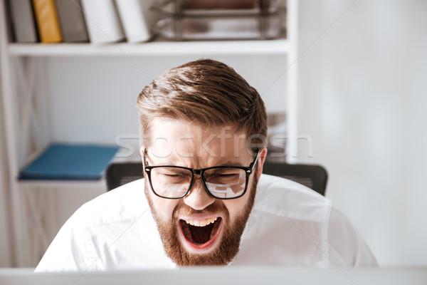 Sikít mérges fiatal üzletember néz számítógép Stock fotó © deandrobot
