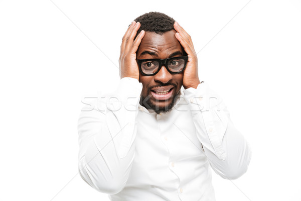 Stock photo: Confused young african man dressed in shirt wearing glasses