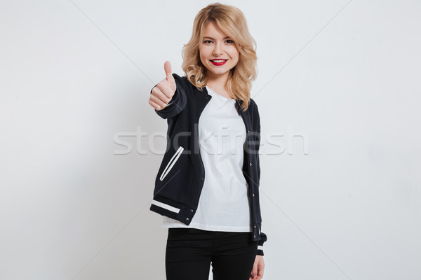 Portrait of a smiling young girl in casual clothes standing and showing thumbs up Stock photo © deandrobot