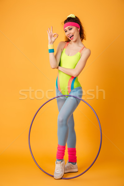 Smiling playful sportswoman holding hula hoop and showing ok sign Stock photo © deandrobot