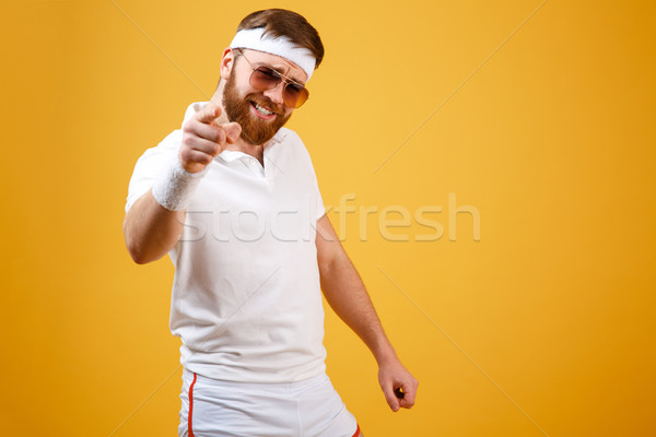 Cool sportsman in sunglasses pointing at camera Stock photo © deandrobot