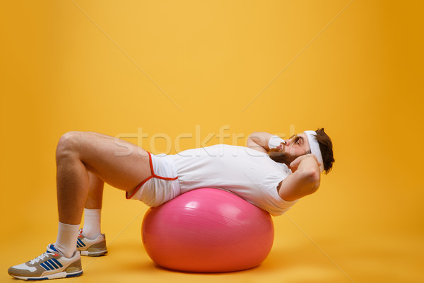 Side view of sportsman lying on fitness ball Stock photo © deandrobot