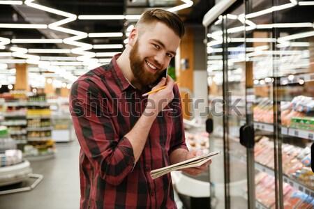 Glücklich junger Mann Supermarkt sprechen Telefon schriftlich Stock foto © deandrobot