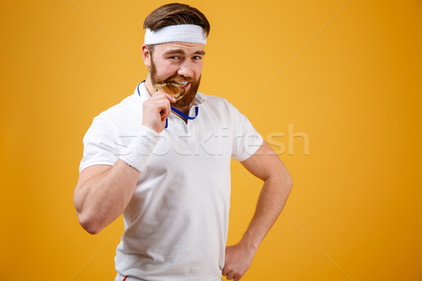 Handsome young sportsman with medal standing isolated Stock photo © deandrobot