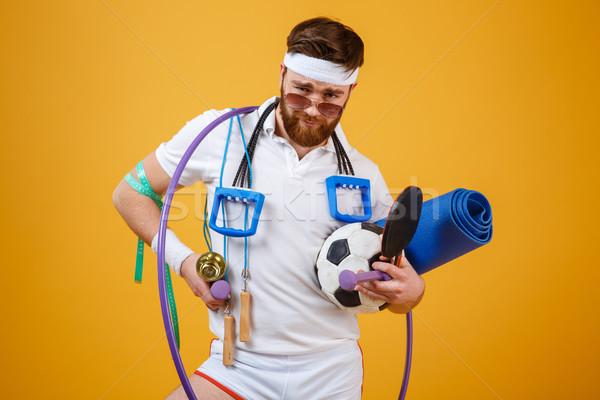 Elégedett szakállas fitnessz férfi napszemüveg tart Stock fotó © deandrobot