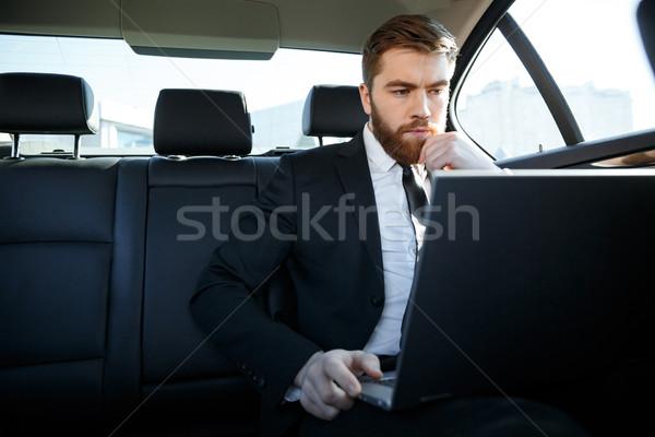 Calme homme d'affaires utilisant un ordinateur portable ordinateur séance Retour Photo stock © deandrobot