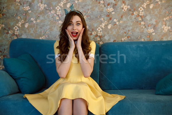 Happy surprised young pin-up lady sitting on sofa Stock photo © deandrobot