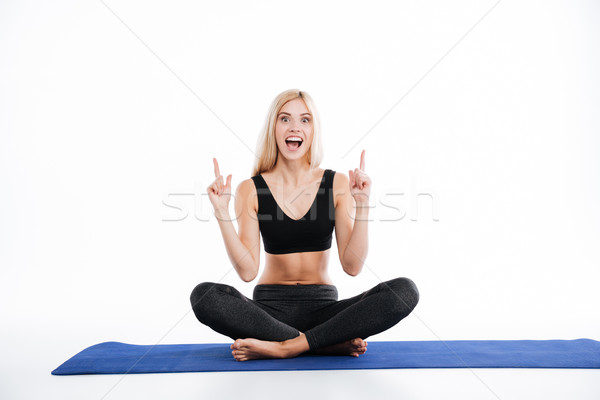 Smiling fitness woman sitting make yoga exercises pointing. Stock photo © deandrobot
