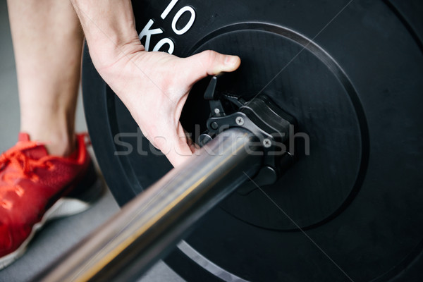 Cropped image of athletic man collects the barbell Stock photo © deandrobot