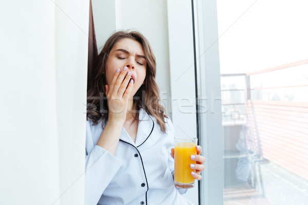 Sleepy young woman in pajamas holding orange juice and yawning Stock photo © deandrobot