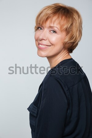 Close up image of happy elderly woman standing sideways Stock photo © deandrobot