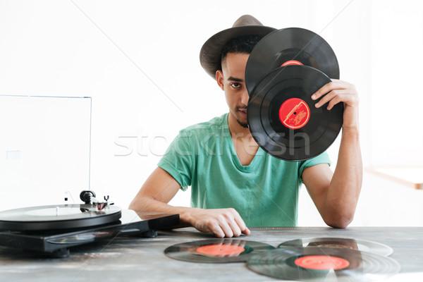Afrikaanse man verbergen achter records groene Stockfoto © deandrobot
