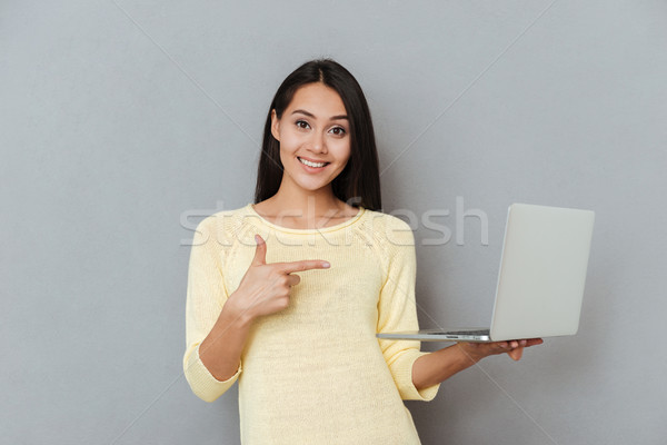 Smiling attractive young woman holding and pointing on laptop Stock photo © deandrobot