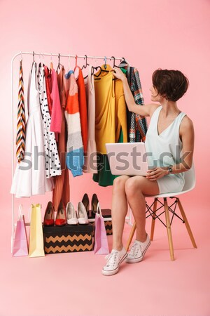 Cheerful young lady sitting on floor near sofa indoors Stock photo © deandrobot