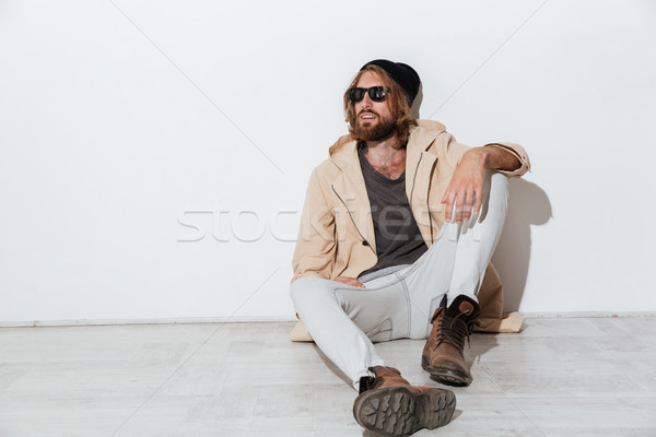 Serious hipster guy looking aside sitting isolated Stock photo © deandrobot