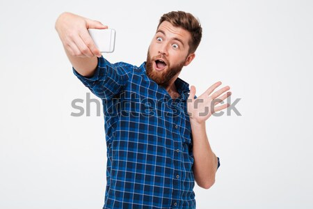 Happy bearded man in checkered shirt playing on his smartphone Stock photo © deandrobot