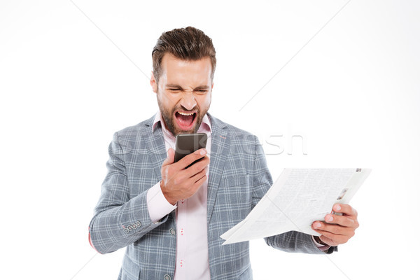 Screaming young man holding gazette and talking by phone. Stock photo © deandrobot