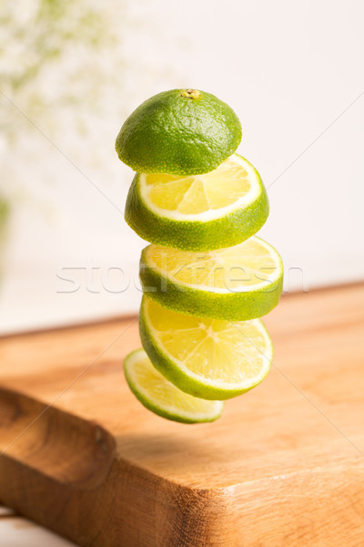 Close up of a sliced whole lime flying Stock photo © deandrobot