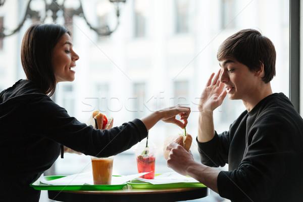 Jeune femme manger Burger frère jeunes cute Photo stock © deandrobot