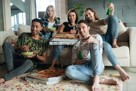 Cheerful young friends eating pizza and talking in living room Stock photo © deandrobot