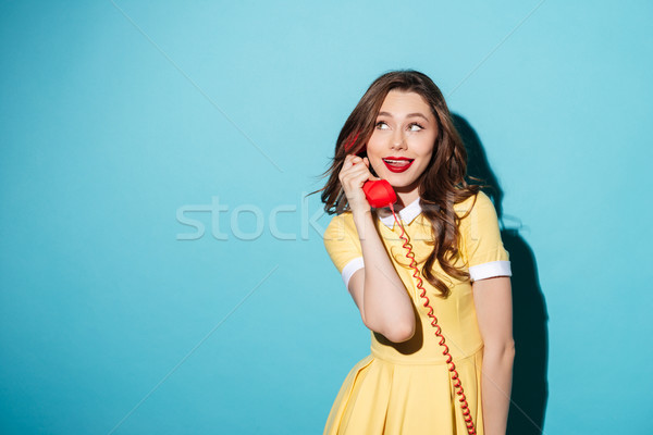 Attractive young girl in dress talking on retro telephone tube Stock photo © deandrobot