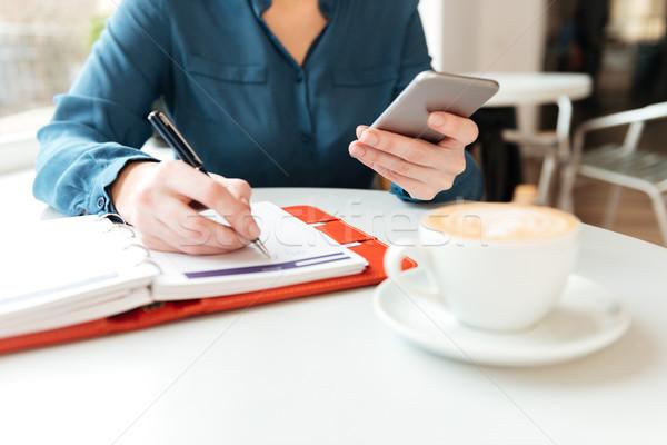 Kép nő kávézó asztal tart mobiltelefon Stock fotó © deandrobot