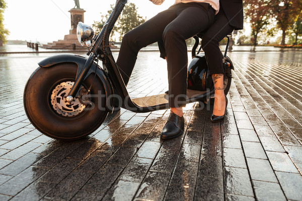 Cropped image of business couple sitting on modern motorbike Stock photo © deandrobot