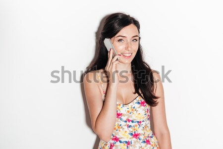 Happy brunete woman talking by smartphone and looking at camera Stock photo © deandrobot