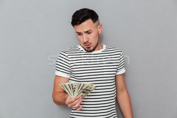 человека футболки глядя деньги Сток-фото © deandrobot