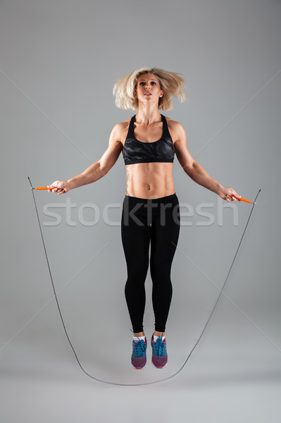 Full length portrait of a concentrated muscular adult sportswoman Stock photo © deandrobot