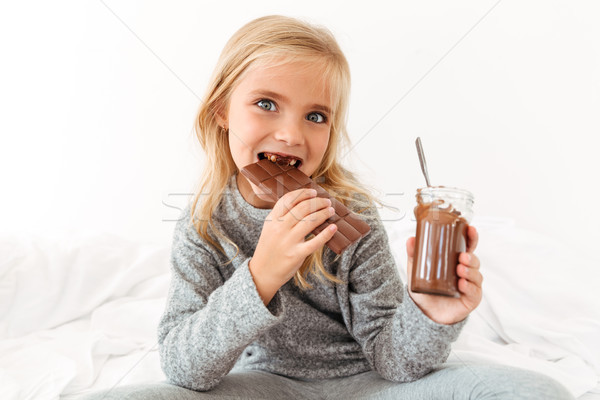 Close-up photo of funny girl eating chocolate bar looking at cam Stock photo © deandrobot