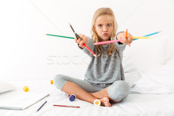 Funny little girl in gray pajamas playing with colorful pencils, Stock photo © deandrobot