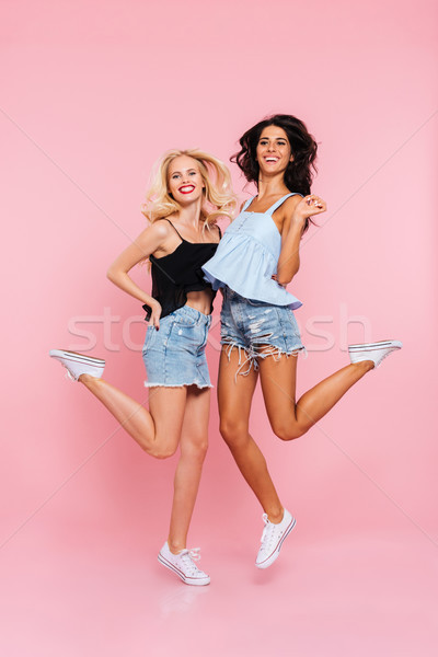 Full length image of two happy women in summer clothes Stock photo © deandrobot