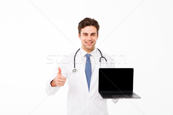 Portrait of a cheery young male doctor with stethoscope Stock photo © deandrobot