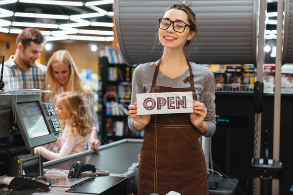 Stock photo: Portrait of friendly woman cashier holding open sign
