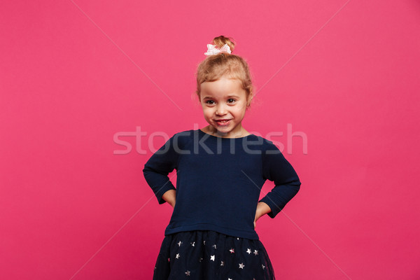 Pretty young girl holding arms on hips and looking aside Stock photo © deandrobot