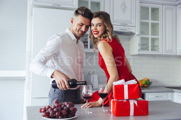 Happy woman looking camera while her man pouring wine into glasses at home Stock photo © deandrobot